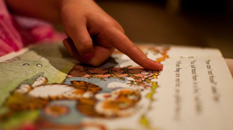 Copil aratand cu degetul carti ilustrate